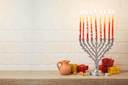 Jewish holiday Hanukkah concept with menorah, gift box and spinning top on wooden table