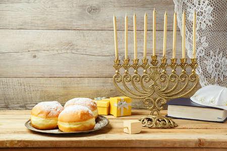 Jewish holiday Hanukkah concept with menorah, sufganiyah, gift box and spinning top on wooden table