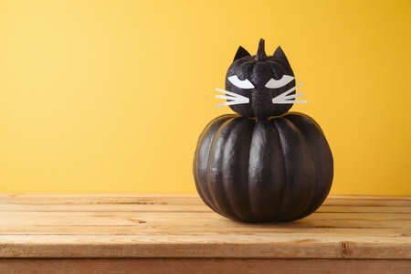 Halloween holiday creative concept with cute funny black pumpkin decor as black cat on wooden table over yellow background 免版税图像