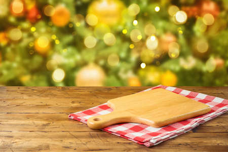 Empty wooden table with cutting board and tablecloth over Christmas tree bokeh background. Holiday product montage display or mock up design 免版税图像