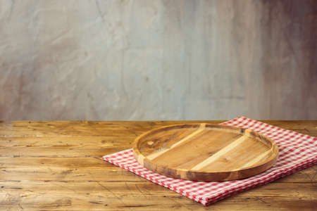 Empty wooden table with tablecloth and wooden board over rustic background. Product montage display or kitchen mock up design Reklamní fotografie