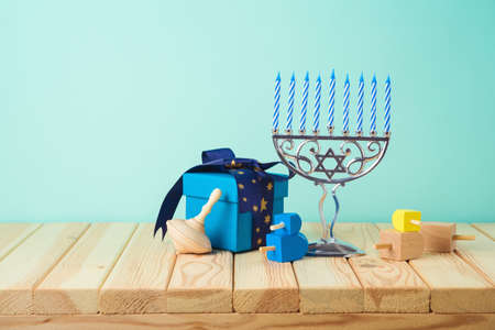 Jewish holiday Hanukkah creative decor background with menorah, gift box and spinning top on wooden table