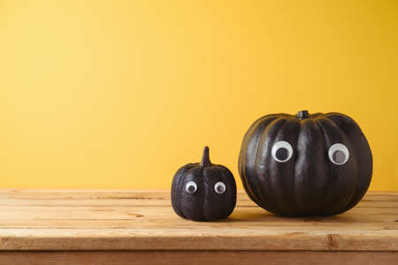 Halloween holiday creative concept with cute funny black pumpkin decor on wooden table over yellow background