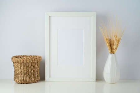 White frame mock up with home decor objects on table background