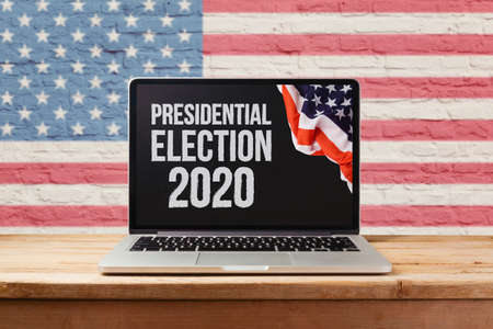 Presidential Election 2020 concept with laptop computer and USA flag  on wooden table over brick wall background