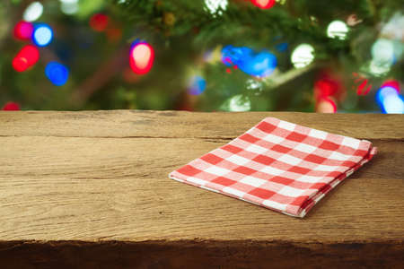 Christmas holiday background with empty wooden table with red checked tablecloth over Christmas tree bokeh. Product montage display or mock up design