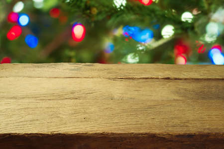 Christmas holiday background with empty wooden table over Christmas tree bokeh. Product montage display or mock up design 免版税图像