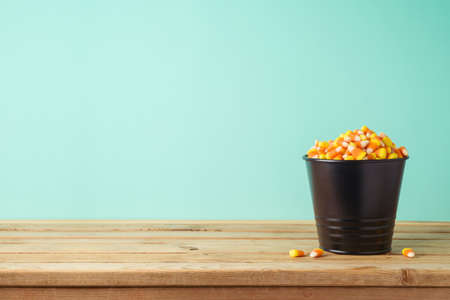 Bucket with candy corn on wooden table. Halloween holiday celebration background