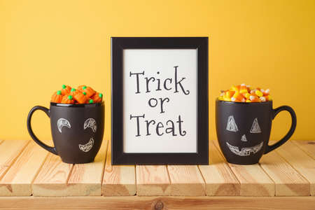 Halloween holiday creative concept with photo frame mock up, chalkboard coffee mugs and candy corn on wooden table