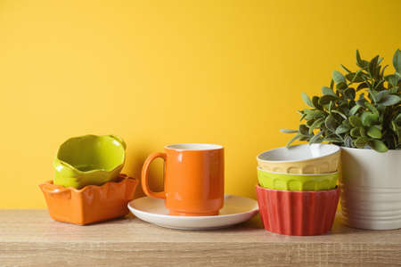 Autumn kitchen interior background with plant, colorful bowls and coffee cup on wooden shelf 免版税图像