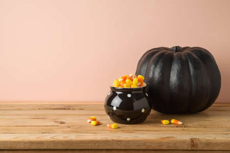 Halloween holiday celebration concept with candy corn and  black pumpkin decor on wooden table 免版税图像