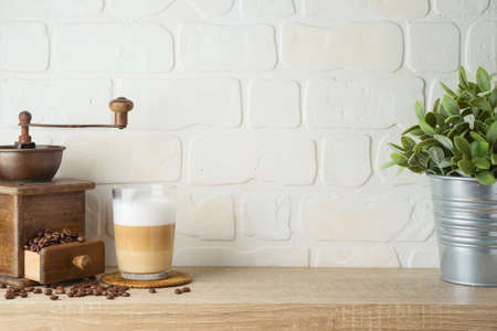 Kitchen background with coffee cup and plant on wooden shelf over brick wall