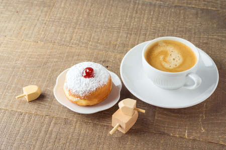 Coffee cup with traditional donuts sufganiyah for Jewish holiday Hanukkah on wooden table.