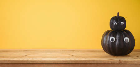 Empty wooden table with Halloween black pumpkin decor over yellow background