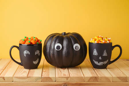 Halloween holiday creative concept with black pumpkin, chalkboard coffee mugs and candy corn on wooden table