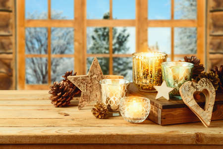 Christmas holiday background with candle decor and pine cone on wooden table over window. Winter greeting card.