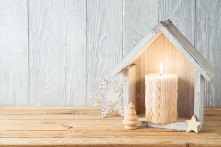 Christmas holiday background with home decor house and candle on wooden table. Winter greeting card. 免版税图像