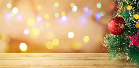 Christmas holiday background with Christmas tree and empty wooden table over festive bokeh