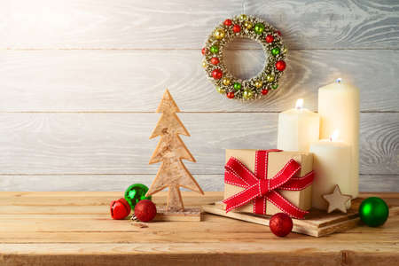 Christmas holiday background with gift box, ornaments and candle decor on wooden table. Winter greeting card.