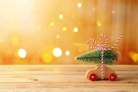Christmas holiday concept with toy car and Christmas tree on wooden table over bokeh festive background 免版税图像