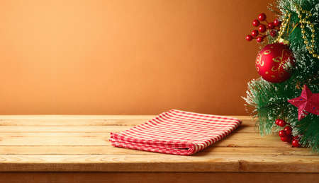 Empty wooden table with red checked tablecloth and Christmas tree. Christmas background for mock up design