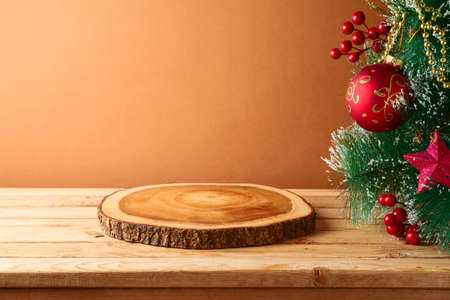 Empty wooden log board on rustic table with Christmas tree. Christmas background for mock up design 免版税图像