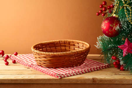 Empty basket on wooden table with tablecloth and Christmas tree. Christmas background for mock up design