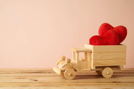 Valentine's Day concept with toy truck and heart shape on wooden table over pink background 免版税图像