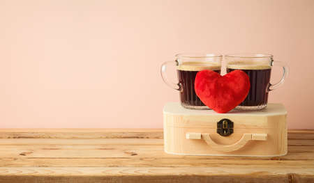 Valentine's Day concept with couple of coffee cups and heart shape on wooden table over pink background