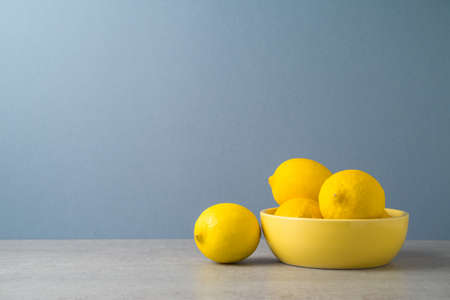 Lemons in yellow bowl over gray background. Modern kitchen mock up for design 免版税图像