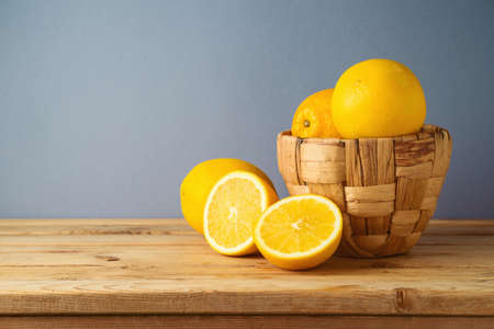 Oranges fruit in basket on wooden table over gray background 免版税图像