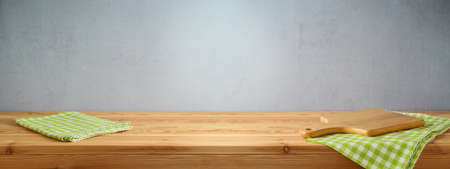 Empty wooden table with tablecloth and cutting board over gray wall background. Spring and easter mock up for design