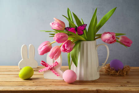 Easter holiday concept with easter eggs and tulip flowers on wooden table 免版税图像