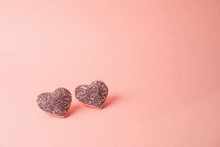 Valentine's day minimal concept with glitter heart shapes over pink background