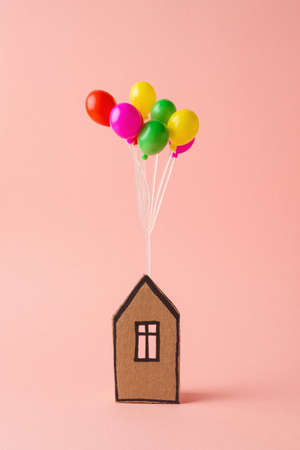 Littlle house with colorful balloons over pink background. Creative real estate business minimal concept 免版税图像