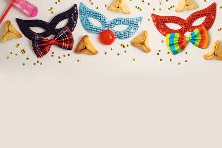 Jewish holiday Purim celebration concept with traditional cookies and carnival mask  on white background with copy space