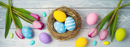 Easter holiday concept with easter eggs in bird nest and tulip flowers on wooden background