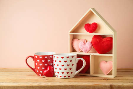 Valentine's Day concept with coffee cup, house toy and heart shape on wooden table over pink background
