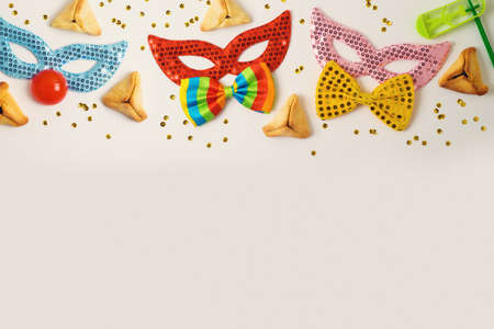 Jewish holiday Purim celebration background with traditional cookies and carnival mask