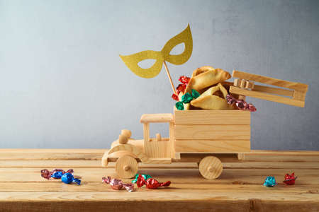 Jewish holiday Purim concept with hamantaschen cookies in toy truck on wooden table 免版税图像