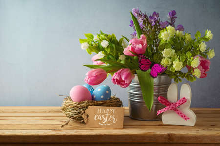 Easter holiday concept with easter eggs in bird nest and beautiful tulip flowers bouquet on wooden table