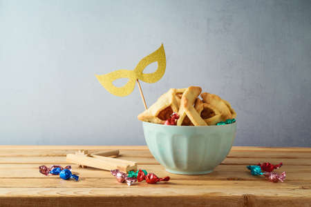 Jewish holiday Purim concept with hamantaschen cookies in bowl on wooden table