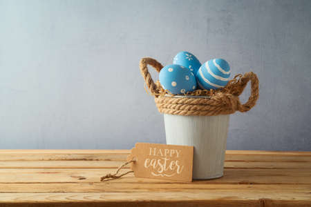 Easter holiday concept with blue easter eggs in bucket on wooden table