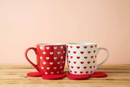 Coffee cups with  heart shapes on wooden table. Romantic couple Valentine's day concept.