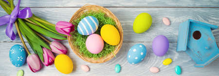 Easter holiday concept with easter eggs in basket and tulip flowers on wooden background 免版税图像