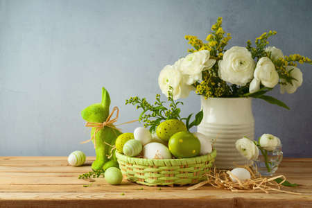 Easter holiday concept with beautiful flowers bouquet and Easter eggs on wooden table