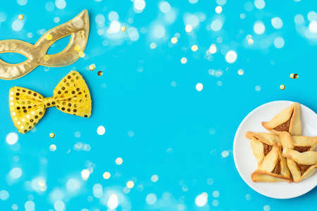 Jewish holiday Purim concept with carnival mask and hamantaschen cookies on blue background