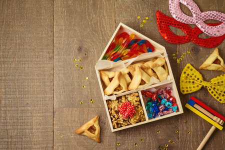 Jewish holiday Purim concept with hamantaschen cookies, walnuts and candy in toy house box on wooden table background. Creative gift box idea