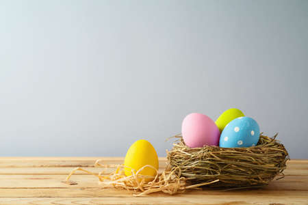Easter holiday background with easter eggs in bird nest on wooden table