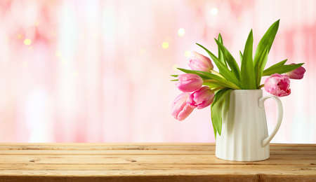 Beautiful tulip flower bouquet on wooden table over pink bokeh background. Valentine's day or mother's day concept